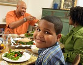 Family Sits at a Table With Food, Boy Looking at Camera