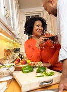 Couple Making a Toast of Red Wine Cooking by Their Kitchen Counter