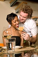 Young Couple having Dinner at Home Man handing Women Rose