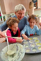 Girls making Cupcakes with Grandmother in Kitchen