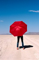 Woman with red umbrella in the Black Rock Desert. Nevada. USA