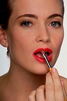 Close-up of a young woman applying lipstick with a brush