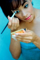 Close-up of a young woman applying eye shadow (thumbnail)