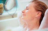 Woman lying with her eyes closed in a bubble bath