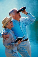 Senior couple looking through a pair of binoculars