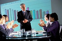 Business executives clapping at a presentation in the conference room