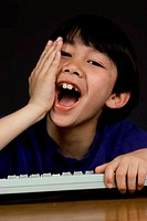 Portrait of a boy holding a computer keyboard laughing