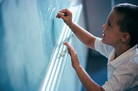 Boy writing on a chalkboard