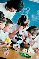 Students looking through a microscope in a classroom