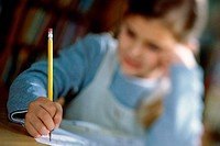 Close-up of a girl sitting and writing with a pencil