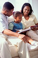 Father and mother sitting on a sofa with their daughter reading a book