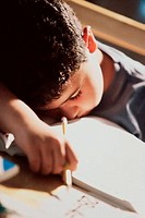 Boy sleeping on a desk holding a pencil