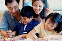 Mother and father with their children coloring together