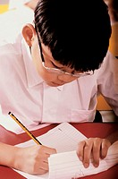 Boy writing on sheets of paper