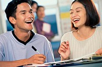 Two teenage students laughing in a class