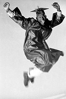Young man wearing a graduation outfit jumping in the air
