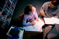 High angle view of a man and a teenage girl studying together