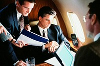 Business executives discussing in a commercial airplane