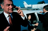 Businessman talking on a mobile phone at the airport
