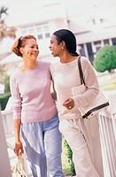 Two women walking on a sidewalk