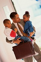 Businessman carrying his son and daughter
