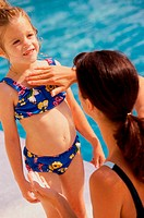 Woman applying sunscreen lotion on her daughter at a poolside