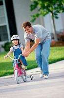 Man teaching his daughter to cycle