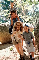 Parents and their two children walking in the forest