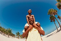 Low angle view of a man carrying his son on his shoulders
