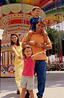 Parents and their two children walking in an amusement park