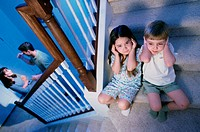 High angle view of a boy and girl listening to their parents fight