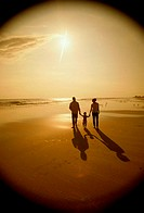 Silhouette of a father and a mother with their daughter at the beach