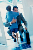 Businessman hugging his son at the door