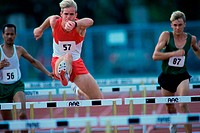 Male runners jumping hurdles in a race