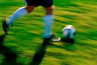 Low section view of a soccer player running with the ball (thumbnail)