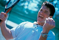 Mid adult man holding a tennis racket raising his hands in excitement (thumbnail)
