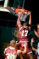 Rear view of a basketball player slam dunking