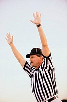 Referee raising his hands blowing a whistle