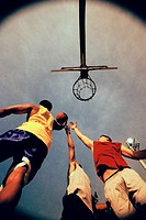 Low angle view of three young men playing basketball