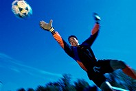 Low angle view of a teenage goalie reaching for the ball