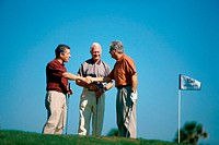 Three people shaking hands at a golf course