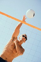 Low angle view of a young man playing volleyball