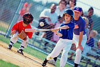 Boy swinging a baseball bat on a field