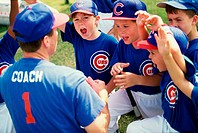 Little league baseball team cheering with their coach
