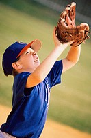 Boy trying to catch a ball with a baseball glove