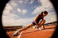 Young female athlete stretching on a running track