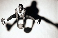 Portrait of a young man holding a basketball jumping up in the air