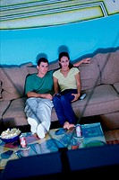 High angle view of a couple sitting on a couch and watching television