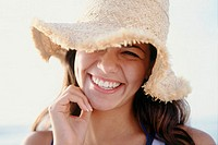 Portrait of a teenage girl wearing a straw hat smiling
