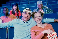 Teenage couple watching a movie in a theater